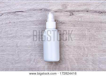 White plastic moisturizer bottle. Inverted bottle on wooden backdrop. Keep your skin moisturized.