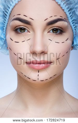 Lovely girl with dark eyebrows and naked shoulders wearing blue medical hat at blue background and looking at camera, plastic surgery, copy space, perforation lines on face.