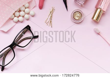 Make up items, gumballs, eyeglasses frame open pink space with room for copy.