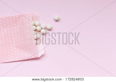 Pink background with a pink polka dot treat bag with white gumballs spilling out. Open space for copy