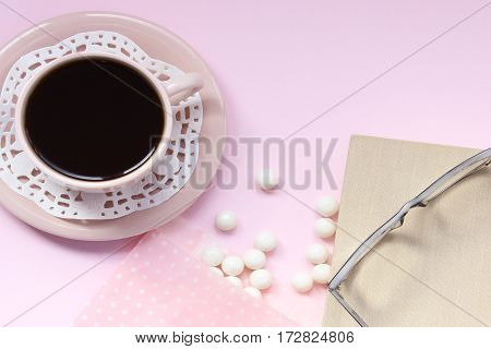 Top view pink background with coffee cup, doily, book, eyeglasses, and white gumballs. Open space for copy