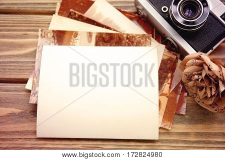 Vintage photos with camera and decorative flower on wooden background