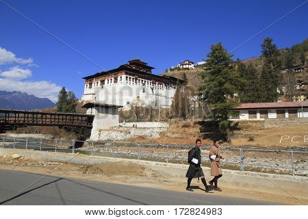 PARO BHUTAN - FEBRUARY 20 2014: Bhutanese young man in traditional clothes walk on the street before Paro Rinpung Dzong castle