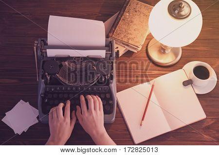 Woman typing on typewriter, top view