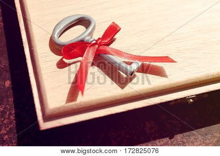 Vintage key with red ribbon on wooden surface