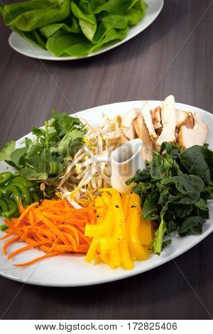 asian chicken lettuce roll plate with ingredients and sauce on wood background