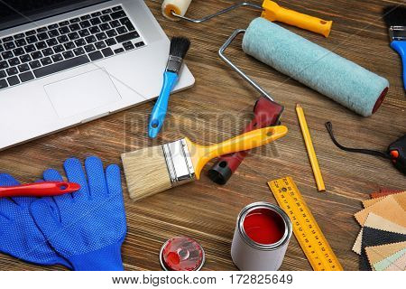 Laptop  and paint tools on wooden table