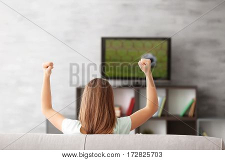 Pretty teenager watching sports on TV at home