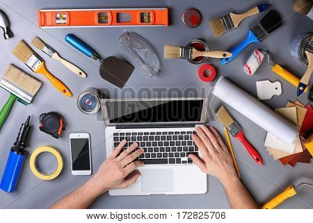 Decorator's hands typing on a laptop. Paint tools on work table