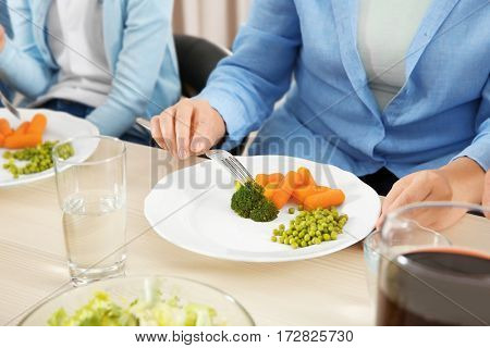 Woman eating vegetables during lunch at home, closeup
