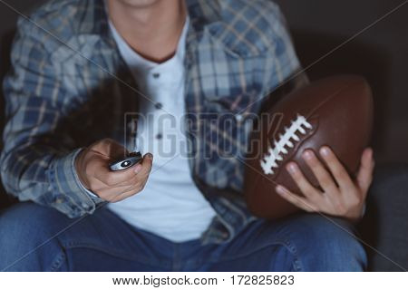Teenager watching rugby late in evening, closeup