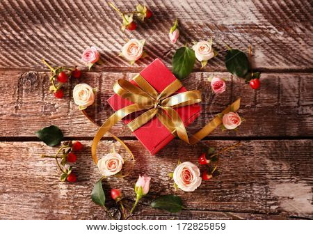 Gift box with flowers on wooden background