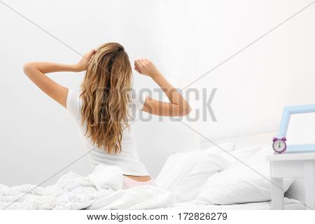 Young attractive woman waking up in the morning