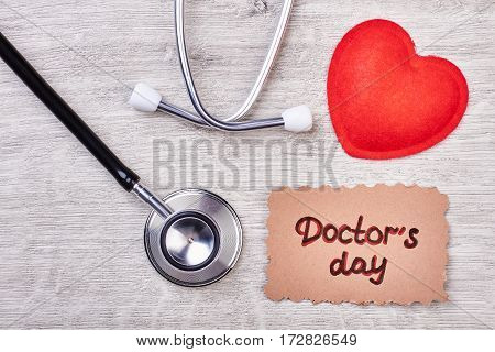Doctor's Day card and stethoscope. Red heart on wooden backdrop. Holiday of noble profession.