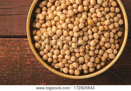 Chick-pea in bowl on wooden background. Horizontal, toned, top view, copy space