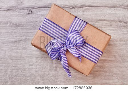 Wrapped gift box with bow. Present on wooden background. Congratulate your relative.