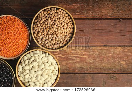 Assorted beans in bowls with red lentil, chick-pea and kidney bean on wooden background. Horizontal, toned, top view, copy space