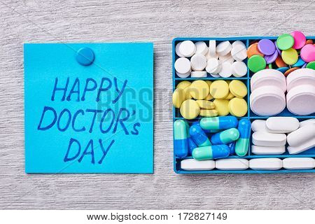 Medical organizer on wooden surface. Congratulation with Doctor's Day.