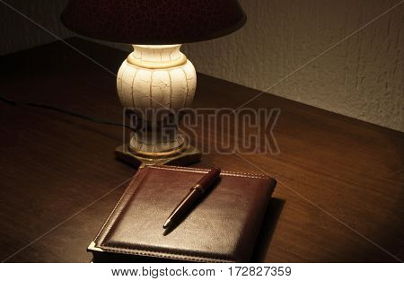 Lamp and notes with pencil on desk