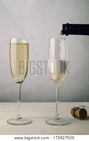 Pair Of Fluted Champagne Glasses Being Filled On Wood Plank Table