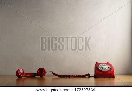 Occupied Retro Red Telephone  With Receiver Trailing Across Desk