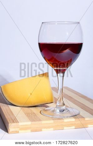 Glass of red red wine grapes and chees on wooden table