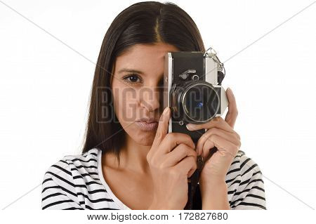 young attractive latin woman taking pictures looking through the viewfinder of an cool retro and vintage photographic camera smiling happy in photography hobby and learning pro photo shooting