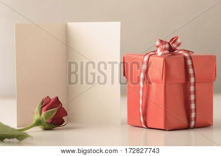 A single small square gift box with lid tied to a bow with gingham ribbon on a white table with a rose and an opened card providing copy space.