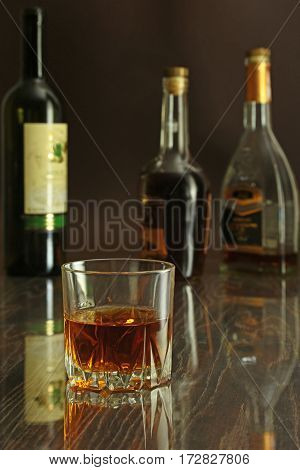 Glass of cognac, brandy or whiscy on mirror table. bottles in a bar on the background.