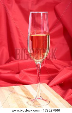 Glass of white wine on red background.