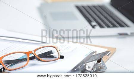 Closeup of white desktop with laptop, glasses, coffee cup, notepads and other items on blurry city background.