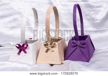 Three Paper Boxes With Bows On White Satin