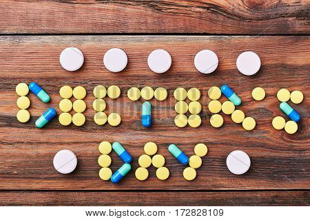 Pills on brown wooden backdrop. White, blue and yellow pills. Celebration of Doctor's Day.