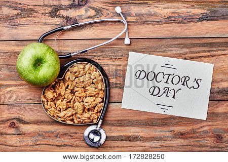 Stethoscope, card, apple and walnut. Warm congratulations with Doctor's Day.