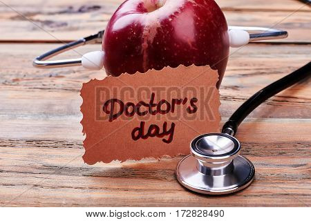 Apple, card, stethoscope on surface. Kind congratulation for Doctor's Day.