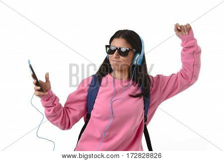 young beautiful woman or happy student girl with sunglasses backpack and mobile phone listening to music with trendy cool headphones singing and dancing ecstatic isolated on white background