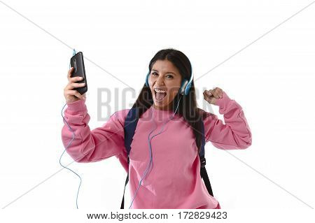 young beautiful woman or happy student girl with backpack and mobile phone listening to music with trendy cool headphones singing and dancing ecstatic isolated on white background