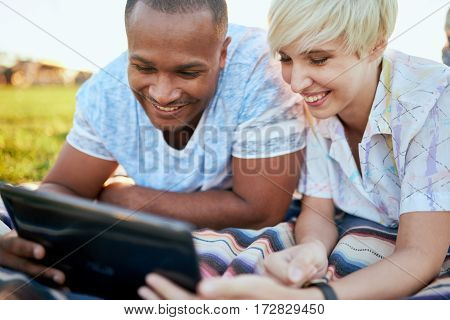 Diverse student friends hanging out in a city parc using digital technology and studying for their next university exam
