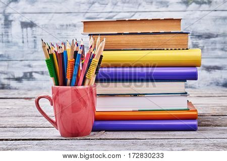 Stack of books on white. Pencils in a red mug. Enjoy studying process.
