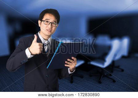Confident Asian Businessman Showing Document File And Giving Thumbs Up In Front Of Meeting Room.