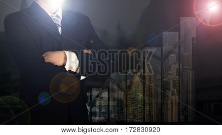 Double Exposure Of Businessman Arms Crossed And Stand Up With Cityscape And Financial Graph Backgrou
