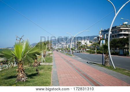 Seaside boulevard in Mediterranean town with cobblestone payvement palms on left and automobile road and residential buildings and hotels on right side with mountains on background shot on sunny day.
