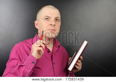 portrait of business man in a pink shirt with a pen and documents