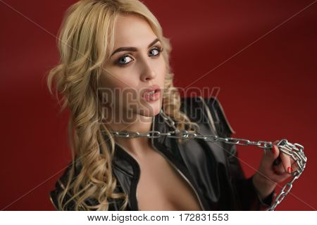 Gorgeous sexy longhaired blonde in black leather jacket and thick metal chain over her neck on red background