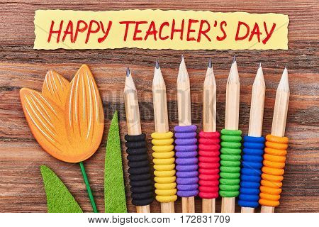 Flower, pencils and greeting card. Creative congratulation for college teacher.