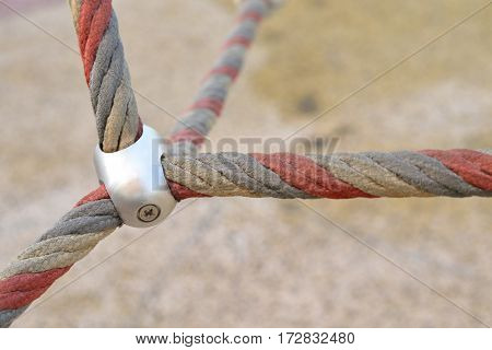 Iron jointed point of ropes in children spider web, use a symbol for teamwork, harmony, rapport or collaboration, outdoor equipment.