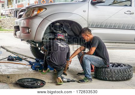 Kota Kinabalu,Sabah-Aug 11,2016:The car mechanics checking shock absorber in car suspension at garage at Kota Kinabalu,Sabah.Shock absorbers can also leak as they are filled with oil.