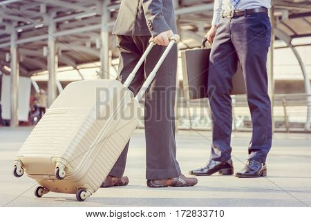 Businessman traveler with luggage at city background