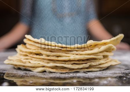 Stack of Homemade Tortillas on floured surface with Woman in Background