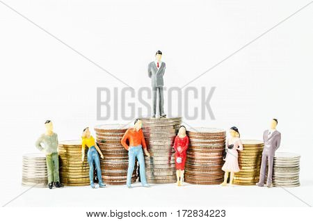 Miniature businessman and people on many stack of coins money on white background.